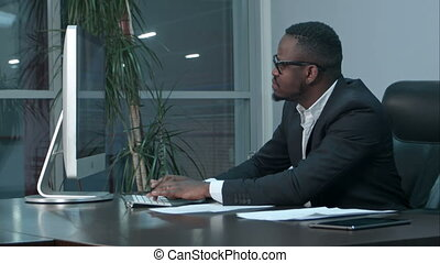 Handsome afro-american businessman working and typing on laptop in the office