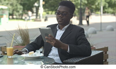 Handsome afro american man is using a tablet, while sitting in outside cafe