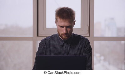 Handsome american businessman typing on laptop in modern ...