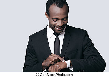 Handsome and confident. Young African man looking on his watch and smiling while standing against grey background