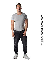 Handsome and fit young man standing in casual, sporty clothes, isolated