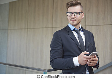 Handsome and pensive businessman with mobilephone