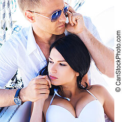 Handsome and rich man and a beautiful and sexy woman in swimsuit relaxing on a sailing boat