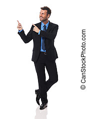 Handsome and smiling businessman pointing at copy space