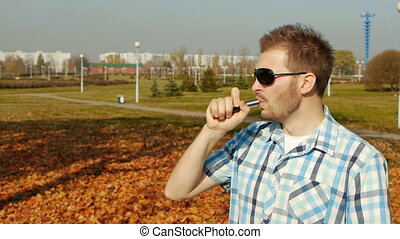Handsome and stylish caucasian man clumsily smokes vape and...