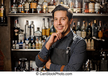 Handsome and young smiling brown haired bartender