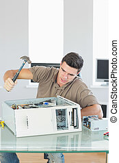 Handsome angry computer engineer destroying computer with...