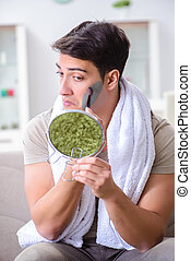 Handsome applying clay mask on face
