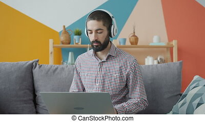 Handsome young Arab guy is working with laptop typing wearing headphones at home. Freelance work, youth culture and apartment activities concept.