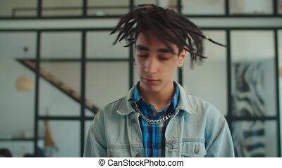 Portrait of handsome carefree young arabic hipster man in casual clothes with dreadlocks waving head over home interior background.