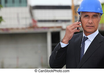 handsome architect making a call in construction site