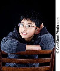 Handsome Asian Chinese boy posing in black hoodie sweater in studio
