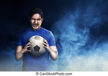 Handsome asian football player holding the ball
