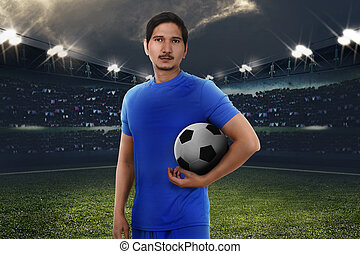 Handsome asian football player with soccer ball
