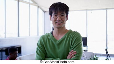 Handsome Asian male executive standing with arms crossed in modern office 4k