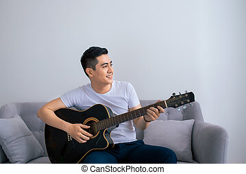 Handsome asian man playing on the guitar on the couch at home