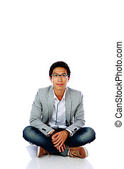 Handsome asian man sitting on the floor over white background
