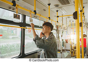 Handsome asian man standing in city bus and talking on mobile phone