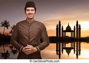 Handsome asian muslim man with traditional dress standing in front of the mosque