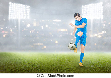 Handsome asian soccer player man in action with ball