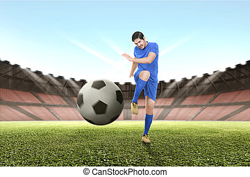 Handsome asian soccer player practicing with the ball