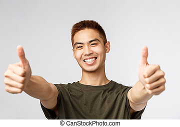 Handsome asian young man with thumb up isolated on white background.