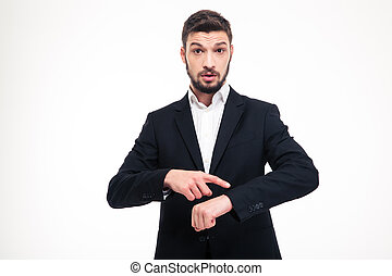 Handsome astonished young business man with beard pointing on watch