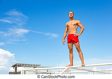 Handsome Athlete Shirtless Young Man stands on a rock against the sky