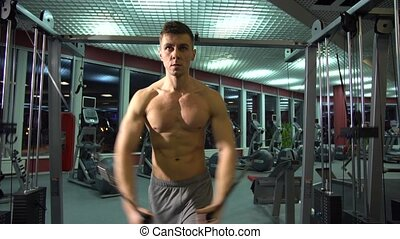 Handsome athletic guy doing pectorals on the crossover trainer in the gym. front view.