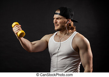 Handsome athletic man doing exercises with yellow dumbbell. be fond of sport
