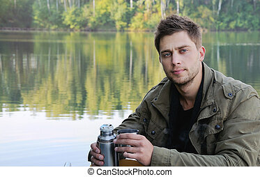 handsome attractive man at the lake on beautiful nature backgrou