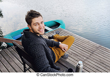 handsome attractive man on the wooden pier at the lake, lifestyl