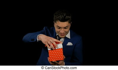Handsome attractive young man opening gift box and showing it to the camera