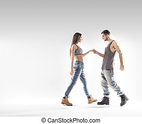 Handsome b-boy dancing with a slim girl