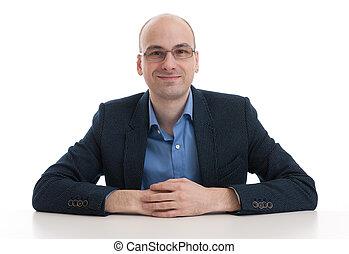 handsome bald man sitting at the desk