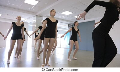 Handsome ballerinas jump with their trainer in classroom....