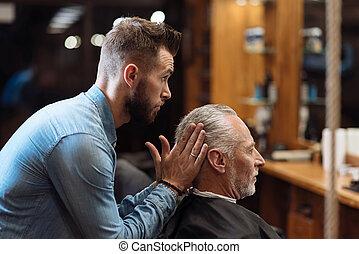 Handsome barber styling hair of senior man