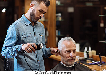 Handsome barber trimming hair of old man