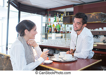 handsome barista making coffee and talking with a female client