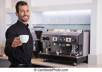 Handsome barista offering a cup of coffee to camera in a...