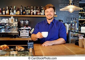 Handsome barista tasting a new type of coffee in his coffee shop