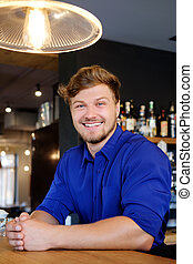 Handsome barman having fun at bar counter in bakery