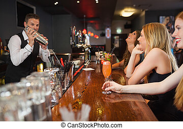 Handsome bartender making cocktails for beautiful women in a...