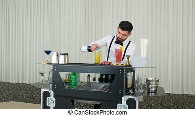 Handsome bartender mixing and preparing a cocktail drink