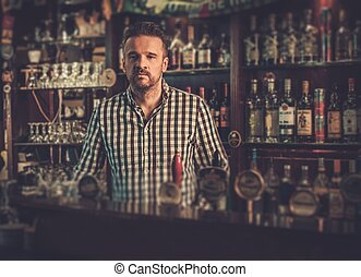 Handsome bartender standing at bar counter in his pub.