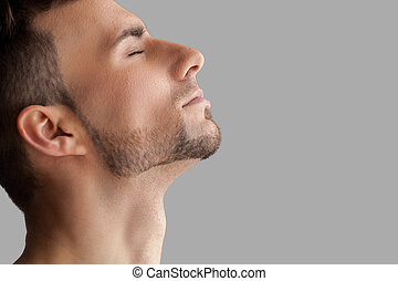 Handsome beard man. Side view of handsome young beard man keeping eyes closed while standing isolated on grey background