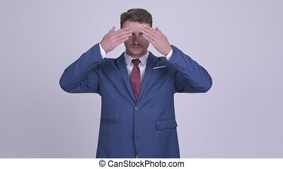 Handsome bearded businessman covering eyes as three wise...