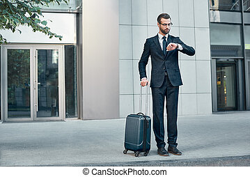 Handsome bearded businessman in classic suit with suitcase is waiting for a taxi