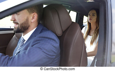 Handsome bearded businessman is sitting in a new car