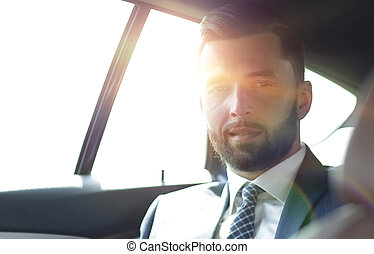 handsome bearded businessman sitting on back seat of car